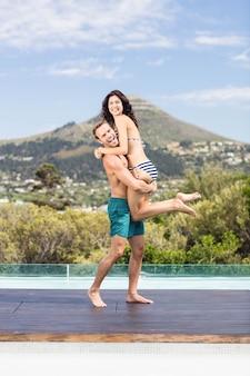 Ritratto di giovane coppia godendo vicino piscina in una giornata di sole