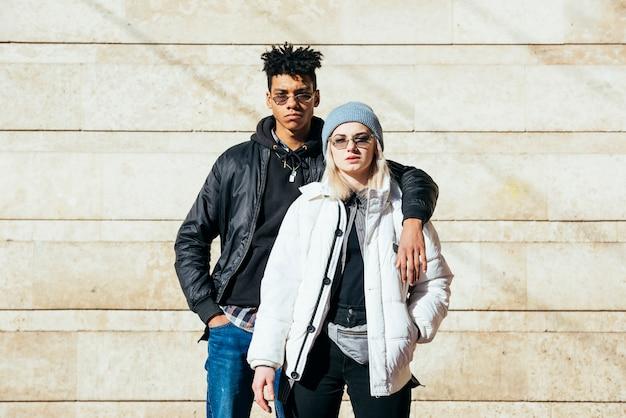 Ritratto di giovane coppia in abiti alla moda in piedi contro il muro