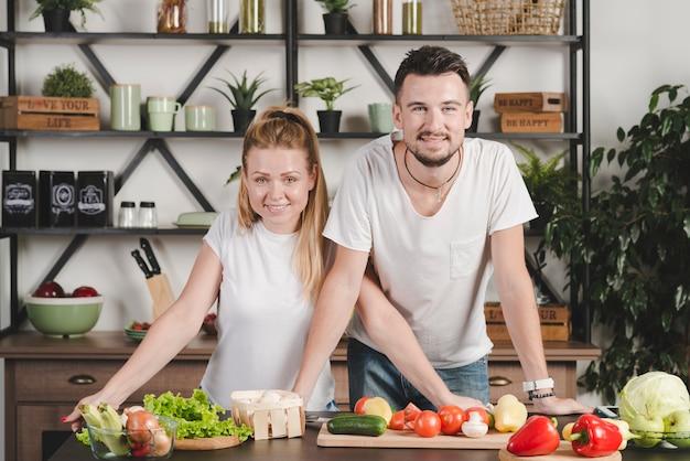 Ritratto di giovane coppia in piedi dietro il bancone della cucina con molte verdure
