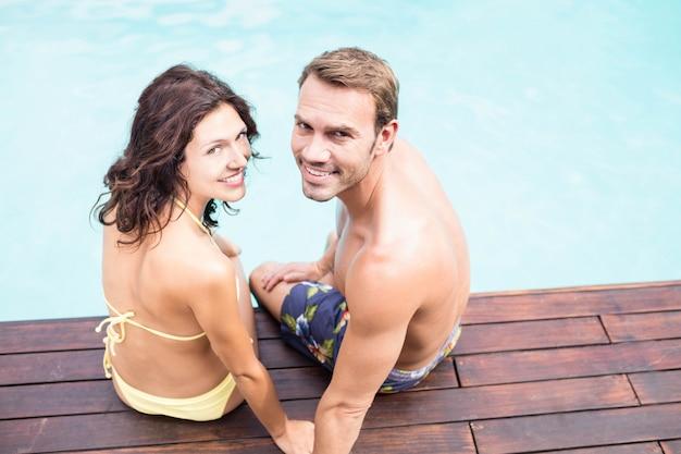 Ritratto di giovane coppia sorridente e seduto a bordo piscina