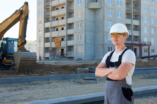 Ritratto di giovane costruttore positivo bello che porta casco protettivo bianco, occhiali protettivi arancioni e tuta da lavoro grigia