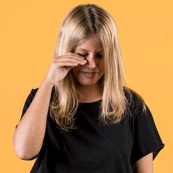 Ritratto di giovane disabile donna che piange su sfondo chiaro