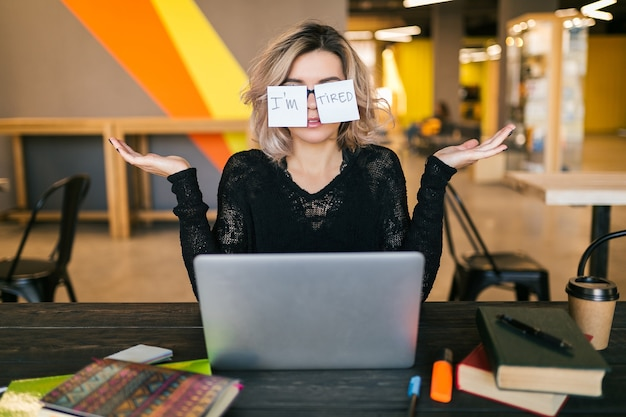 Ritratto di giovane donna abbastanza stanca con adesivi di carta sui vetri che si siedono al tavolo in camicia nera