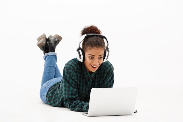 Ritratto di giovane donna africana con il computer portatile su bianco