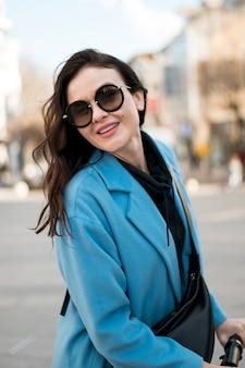 Ritratto di giovane donna alla moda con gli occhiali da sole