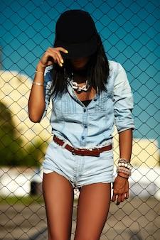 Ritratto di giovane donna alla moda moderna urbana in jeans casual pantaloncini di stoffa all'aperto in strada in berretto nero