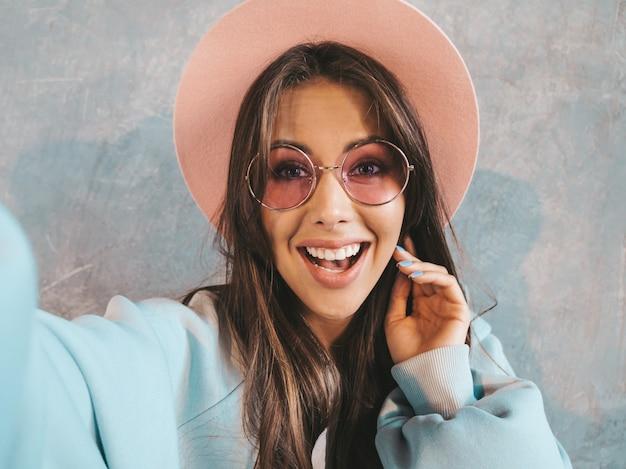 Ritratto di giovane donna allegra che prende il selfie della foto con ispirazione e che indossa vestiti e cappello moderni. in occhiali da sole