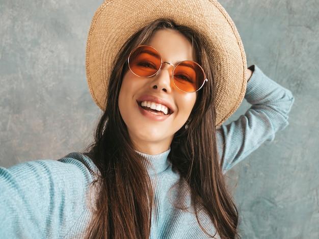 Ritratto di giovane donna allegra che prende il selfie della foto e che indossa vestiti e cappello moderni.