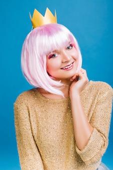 Ritratto di giovane donna allegra con capelli rosa tagliati, in maglione dorato e corona sulla testa sorridente. esprimere positività, emozioni vere, celebrare una grande festa di capodanno.