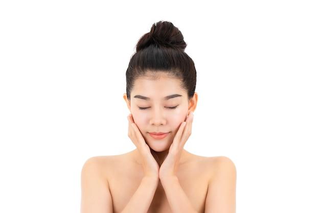 Ritratto di giovane donna asiatica attraente con la pelle e il viso di bellezza isolati su superficie bianca. concetto di cura di pelle e viso sani.