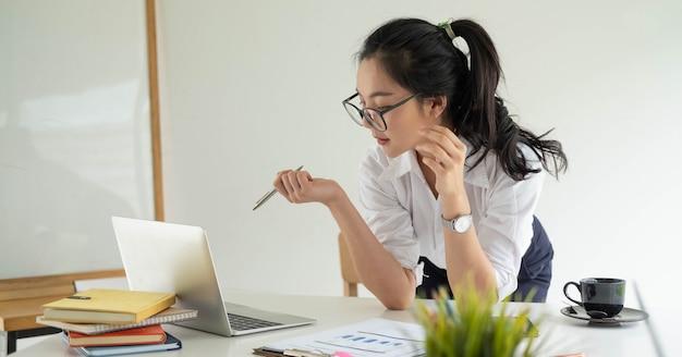 Ritratto di giovane donna asiatica attraente dell'imprenditore di affari che lavora all'ufficio moderno
