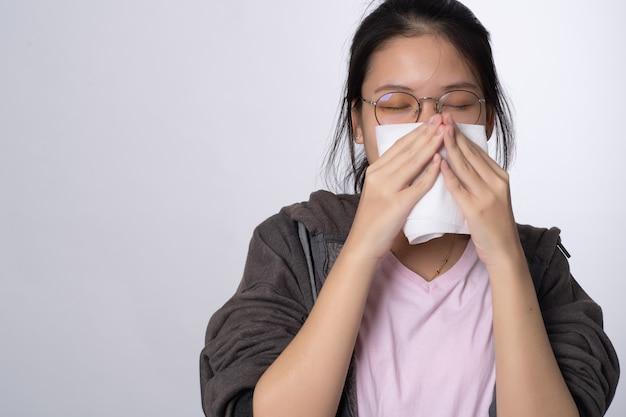 Ritratto di giovane donna asiatica che soffia il naso sul tessuto su grigio
