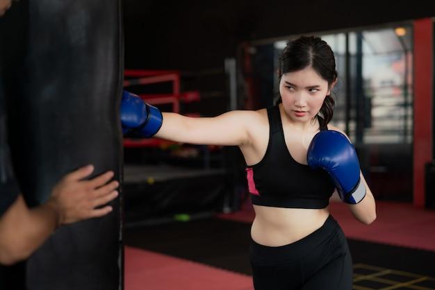Ritratto di giovane donna asiatica sicura del pugile con guantoni da boxe blu, punzonatura di una borsa con trainer in palestra professioal. vestibilità sportiva per stile di vita sano modello asiatico del concetto di palestra di boxe.