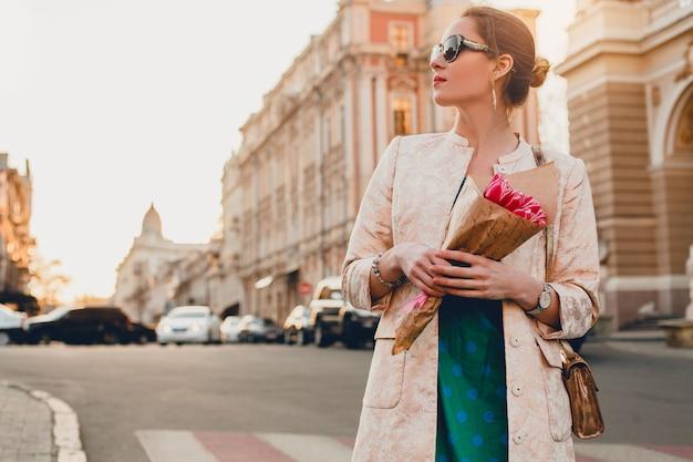 Ritratto di giovane donna attraente alla moda che cammina in città