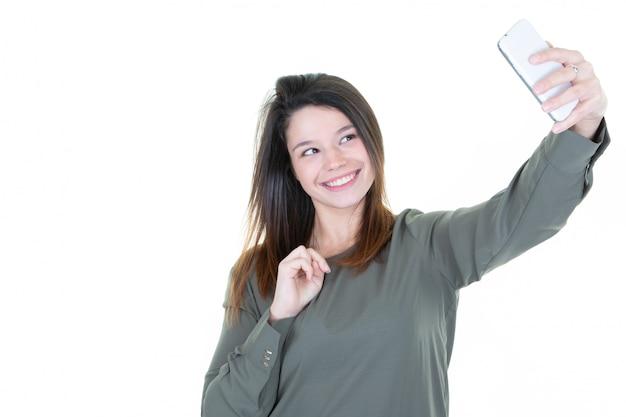 Ritratto di giovane donna attraente che fa la foto del selfie con lo smartphone su fondo bianco