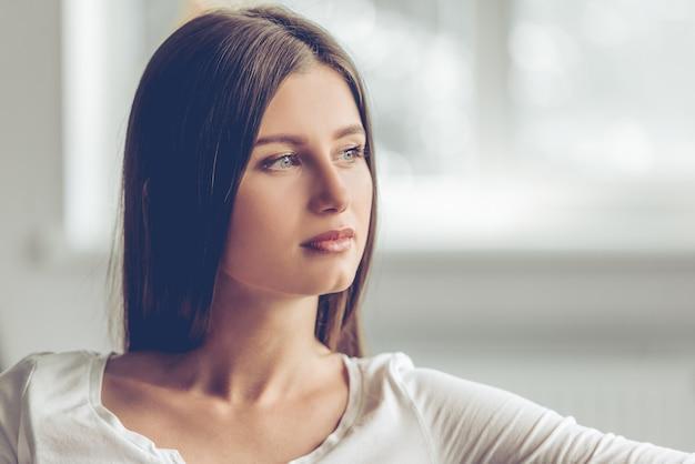 Ritratto di giovane donna attraente che osserva via.