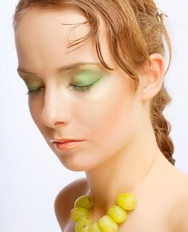 Ritratto di giovane donna attraente con grappolo d'uva