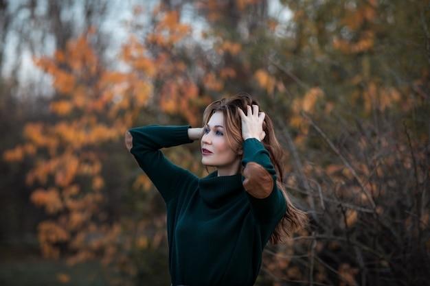 Ritratto di giovane donna attraente del brunette che propone nella sosta di autunno. copia spazio.