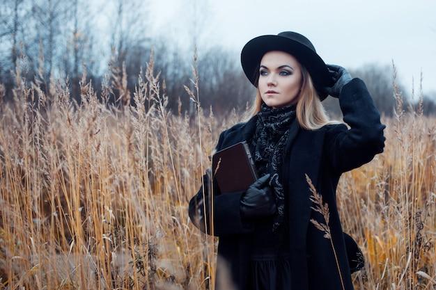Ritratto di giovane donna attraente in cappotto nero e cappello