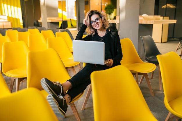 Ritratto di giovane donna attraente seduto in aula, lavorando su un computer portatile, con gli occhiali, aula, molte sedie gialle, apprendimento degli studenti, istruzione online
