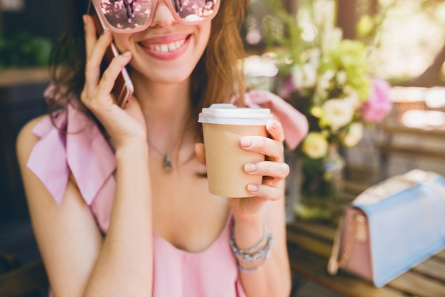 Ritratto di giovane donna attraente seduto nella caffetteria, vestito di moda estiva, abito di cotone rosa, occhiali da sole, sorridente, bere caffè, accessori eleganti, abbigliamento alla moda, parlando al telefono