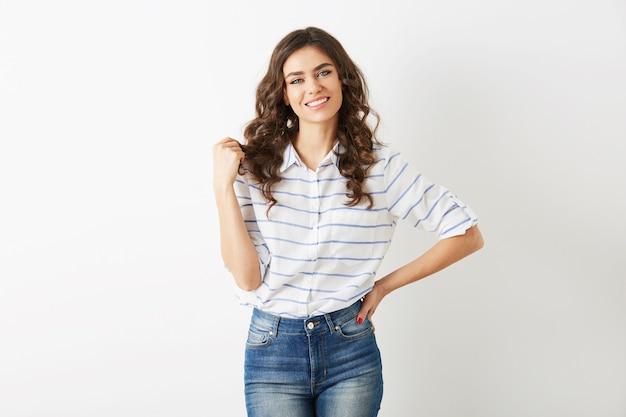 Ritratto di giovane donna attraente vestita in stile estivo moda casual, camicia e jeans, capelli ricci, sorridente, guardando a porte chiuse, bellissimo modello isolato, denti bianchi, bel viso, posa rilassata