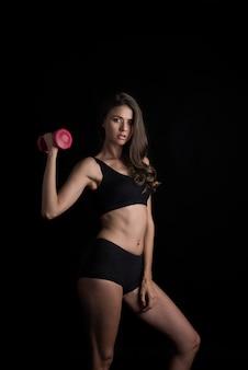 Ritratto di giovane donna bella fare esercizi fisici con manubri