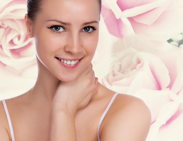 Ritratto di giovane donna bellissima con pelle sana. sfondo di rose
