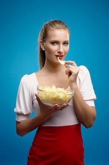 Ritratto di giovane donna bionda alla moda in abito rosa-rosso, belle labbra, trucco luminoso holding, mangiare patate fritte, patatine fritte, patatine e in posa sul muro blu.