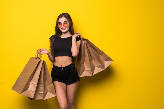 Ritratto di giovane donna bionda allegra in cappello ed occhiali da sole di estate che tengono i sacchetti della spesa sopra la parete gialla
