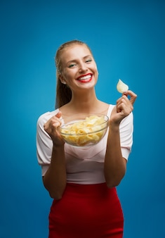 Ritratto di giovane donna bionda che mangia patatine e che tiene una ciotola di vetro