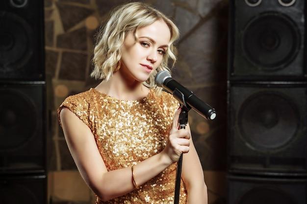 Ritratto di giovane donna bionda con microfono su oscurità