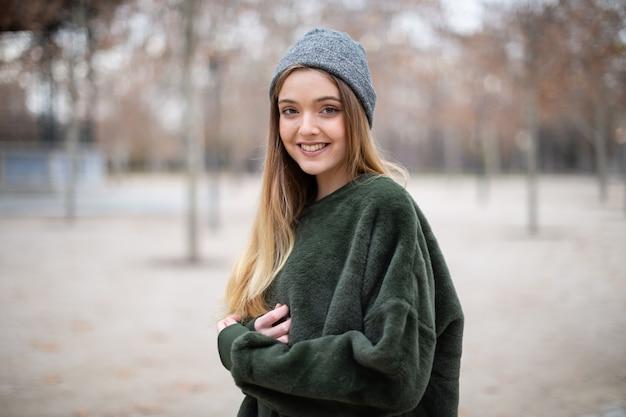 Ritratto di giovane donna bionda sorridente felice con il cappello di inverno in un parco in autunno