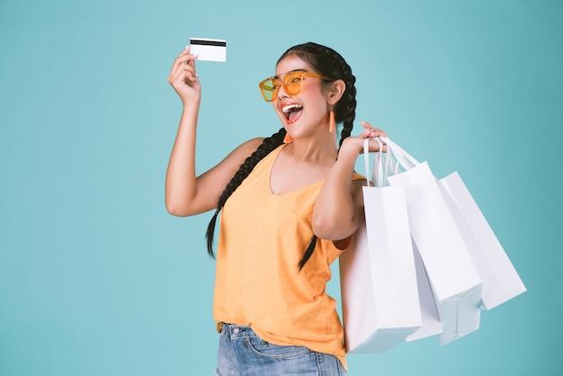 Ritratto di giovane donna bruna in possesso di carta di credito e shopping bags