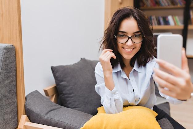 Ritratto di giovane donna castana abbastanza sorridente in occhiali neri rilassante sul divano in appartamento moderno. usare il telefono, fare selfie, sorridere, umore allegro.