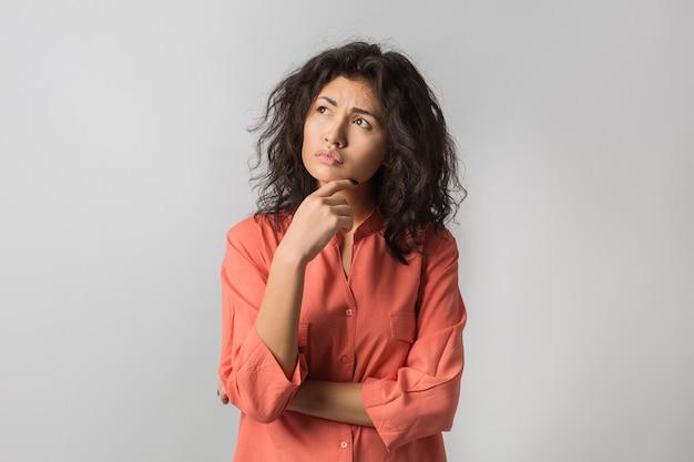 Ritratto di giovane donna castana premurosa in camicia arancione