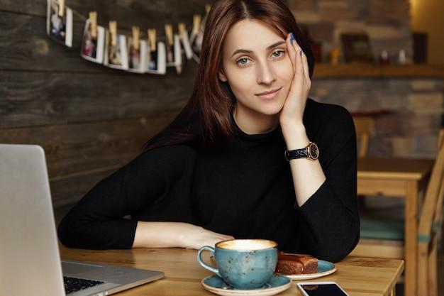 Ritratto di giovane donna caucasica annoiata in abiti neri, faccia pendente a portata di mano