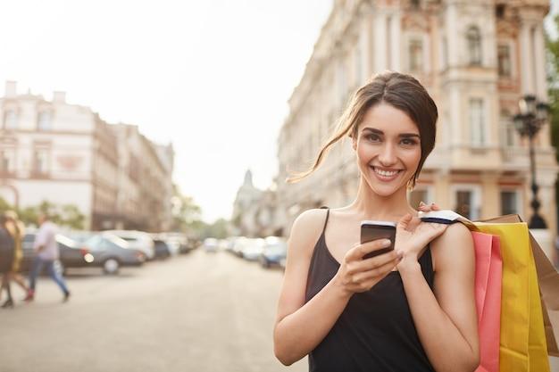 Ritratto di giovane donna caucasica attraente allegra con capelli scuri in vestito nero che sorride a porte chiuse con i denti, tenendo i sacchetti della spesa e lo smartphone in mani, catturando con l'amico. focalizzazione morbida
