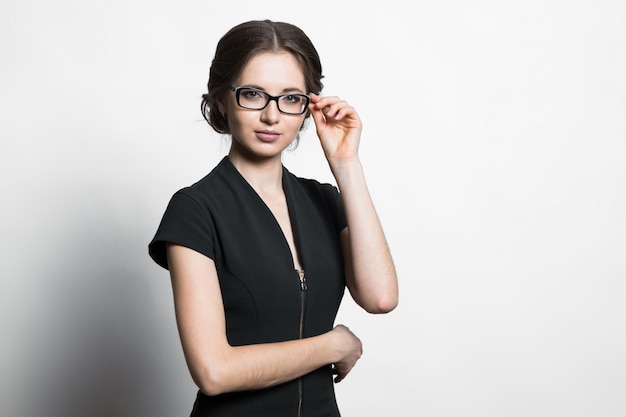 Ritratto di giovane donna caucasica attraente di affari che tiene i vetri con la sua mano su gray