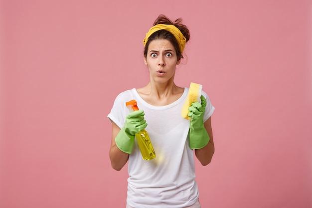 Ritratto di giovane donna caucasica stressata e terrorizzata vestita casualmente in preda al panico mentre deve pulire le stanze velocemente prima che arrivino gli ospiti, tenendo in mano uno spray detergente e una spugna