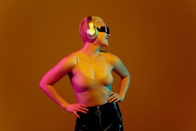 Ritratto di giovane donna caucasica su sfondo marrone con copyspace, aspetto insolito e strano