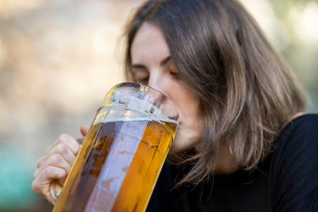 Ritratto di giovane donna che beve birra al bar