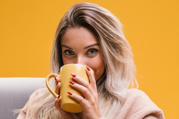 Ritratto di giovane donna che beve il caffè a casa