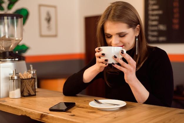 Ritratto di giovane donna che beve il caffè nella caffetteria.