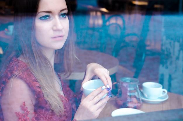 Ritratto di giovane donna che beve tè e guardando fuori dalla finestra