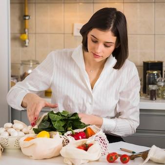 Ritratto di giovane donna che controlla generi alimentari