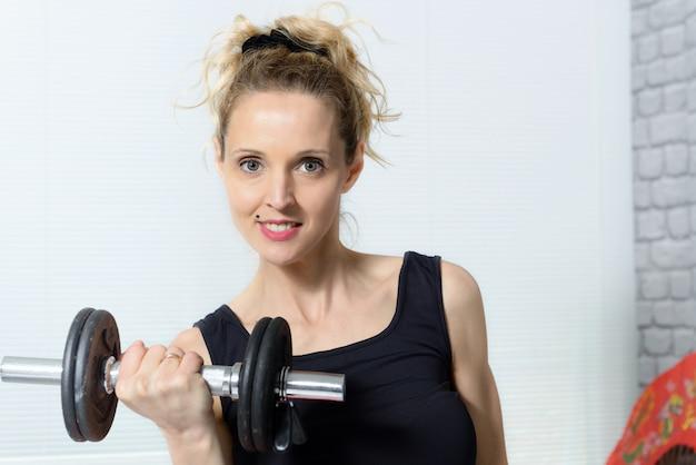 Ritratto di giovane donna che fa esercizio di fitness con manubri, a casa
