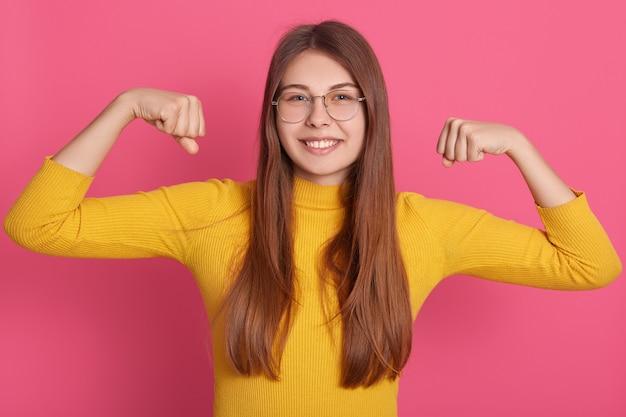 Ritratto di giovane donna che flette i muscoli e che sorride contro la parete ottimistica. modello femminile europeo in abbigliamento casual che mostra i suoi muscoli