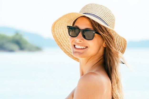 Ritratto di giovane donna che indossa un cappello di paglia sulla spiaggia con vista sul mare