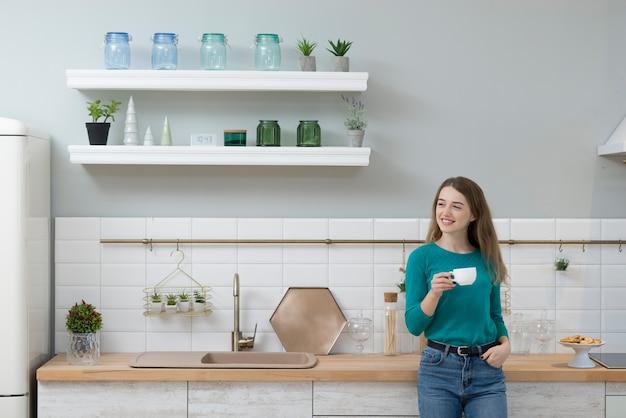 Ritratto di giovane donna che mangia caffè a casa